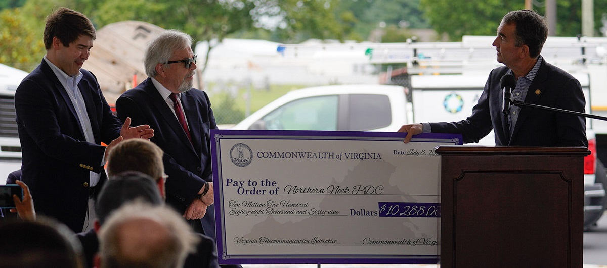 Governor Ralph Northam presenting a check from the Virginia Telecommunication Initiative (VATI) for $10,288,069 to Jerry W. Davis, Executive Director of the Northern Neck Planning District Commission, with Jimmy Carr, CEO of All Points Broadband, standing next to Davis.